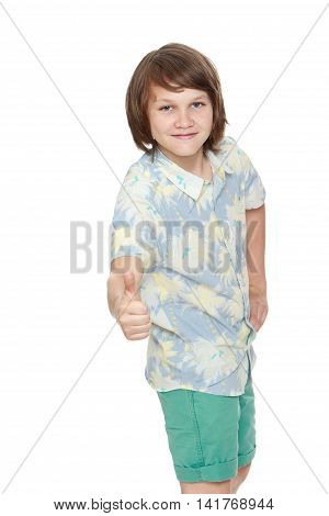 Portrait of a smiling boy in shorts and shirt with short sleeves. The young man raised his thumb to the top. Close-up  - Isolated on white background