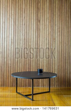 Dark wooden round table with metal legs on the background of the wooden wall. There is a dark glass box on the table. On the floor there is a parquet. Indoors. Horizontal.