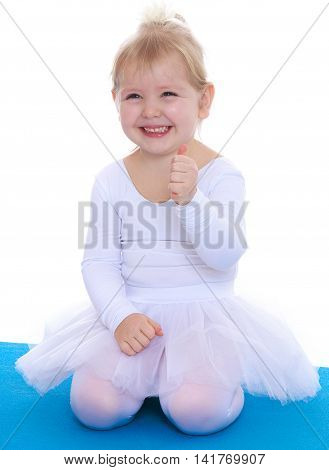 Joyful little girl , a future gymnast, white sports dress kneeling on a blue gym Mat-Isolated on white background