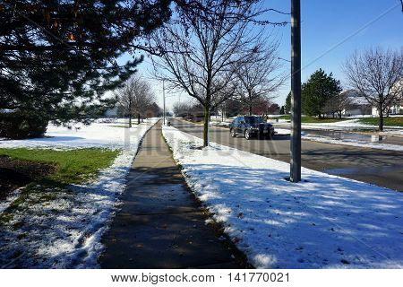 JOLIET, ILLINOIS / UNITED STATES - NOVEMBER 24, 2015: The sidewalk along the Wesmere Parkway in Joliet, Illinois, after a November snow storm.