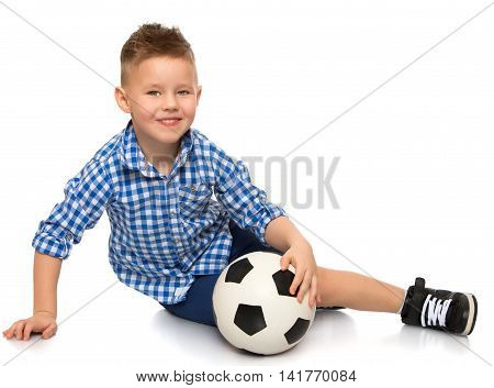 Cheerful little boy in a plaid shirt and blue shorts sitting on the floor clasping a hand soccer ball - Isolated on white background