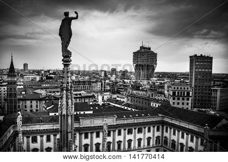 A statue on the cathedral dominates moody black and white view across the Italian city of Milan