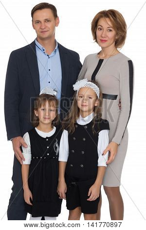 Happy Young family of 4 people . Mom, dad, and two adorable schoolgirl daughter -  Isolated on white background