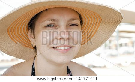 A woman is shown at the beach with style attire. One can still be fashionable and in trend while traveling. A nice jute straw hat completes the look.