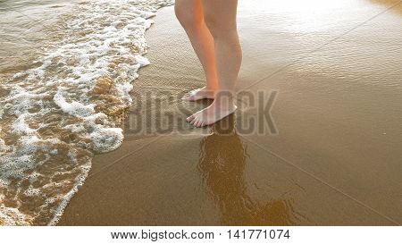 A female is standing on the wet sand close to the waves at the beach. Cold water mixed with sand gives both warmth and coolness. Sunny bright day.