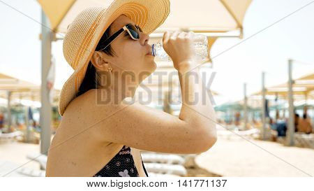 A female is quenching her thirst by drinking water at the beach. On a hot summer day one needs to stay hydrated. Water helps you stay healthy.