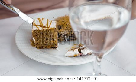 A half filled glass with water is placed on the table with a plate of food next to it. A person is slicing the food with for and a knife. Hydration is important.