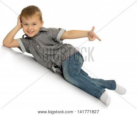 Laughing little boy in jeans and a gray shirt. The boy lies on the floor at an angle and points the index finger in the direction - Isolated on white background