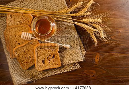 Jar with honey rye bread a spoon of honey and spikelets on sackcloth wooden table