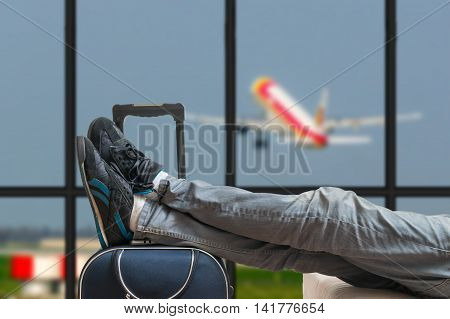 Delayed aeroplane concept. Tired passenger is awaiting airplane arrival in airport terminal.