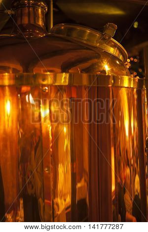 Large copper container for whisky many reflections of light.