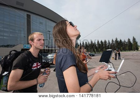Saint-Petersburg Russia - July 23 2016: Young people watch as a young woman in sunglasses controlled drone with a remote control.