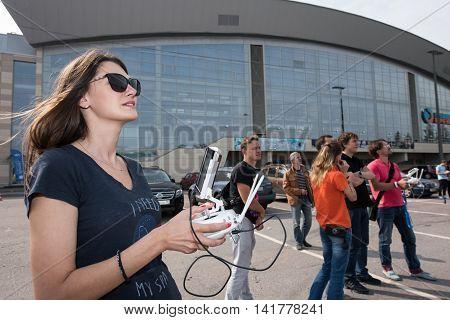 Saint-Petersburg Russia - July 23 2016: A young woman in sunglasses looking up driving drone via remote control.