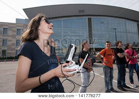 Saint-Petersburg Russia - July 23 2016: Girl happily smiling driving drone by remote control.