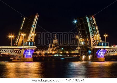 Night view on illuminated open Blagoveshchenskiy Bridge Neva River and Assumption Church on Vasilyevsky Island St. Petersburg Russia