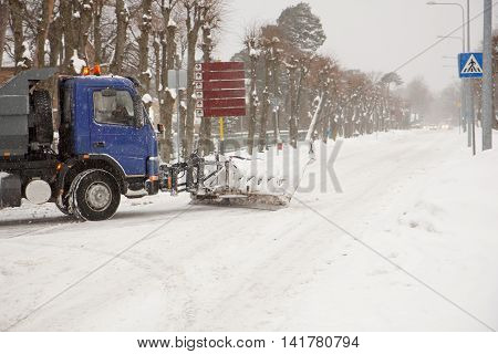A truck cleaning snow off of the road
