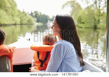 Mother And Sons Enjoying Day Out In Boat On River Together