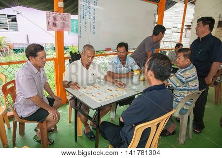 Palau Ketam, Malaysia October 10, 2013; Malaysian men under a leantoo playing intently concentrating on their game checkers on island village of Palua Ketam