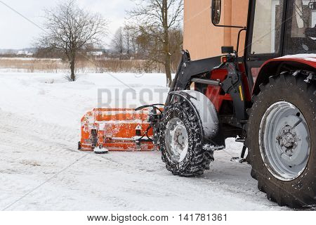 A tractor cleaning snow off from the road