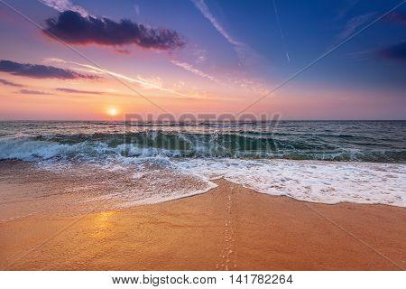 Sunrise light shining on ocean waves. Blue sky.