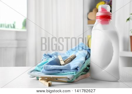 Clean clothes with pins and detergent on table