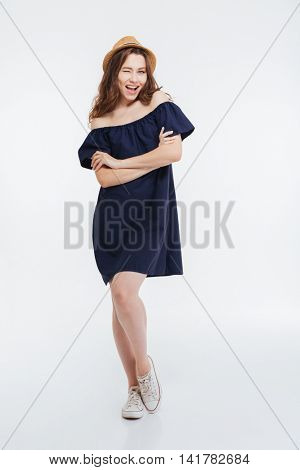 Full length of happy playful young woman in hat standing and winking over white background