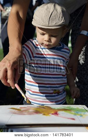 Parent Helping Son To Paint