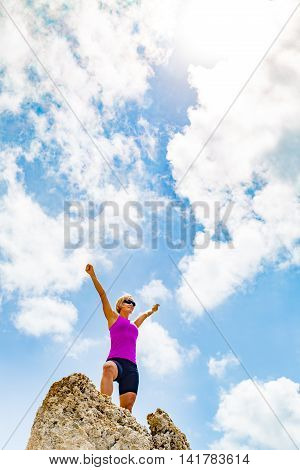 Happy smiling woman on successful climbing running or hiking accomplishment concept celebrating with arms up outstretched trail running outdoors. Sport and fitness inspiration and motivation.