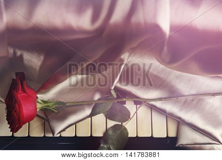 Red rose with with silver cloth on piano