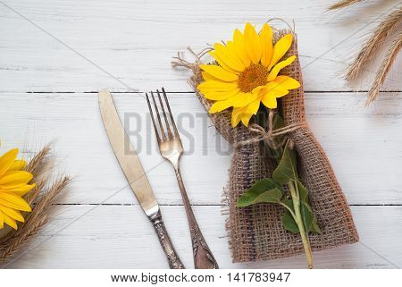 Autumn table setting with silverware and sunflower on white wooden table. Top view. Thanksgiving