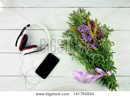 Long walks in nature with a mobile phone. Family leisure Recreation. Modern technology in our lives. Walk with music. Smatrfon headphones and a bouquet of field flowers on a wooden background. Top view. Summer holidays in the countryside.