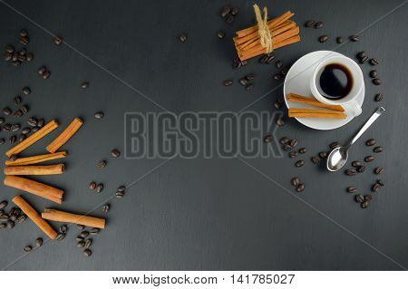 coffee cup and beans cinnamon stickson wooden table on black background. Coffee beans. Top view. Selected focus.