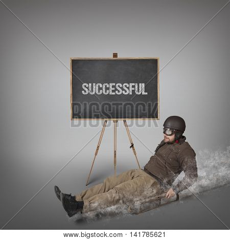 Successful text on blackboard with businessman sliding with a sledge