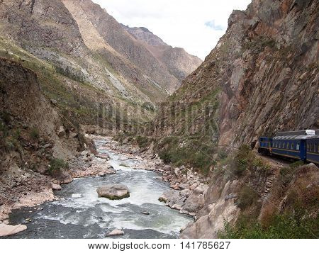 Blue train in a mountain landscape next to a white water river heading from Cuzco through the sacred valley to the Inca city of Machu Picchu in Peru.