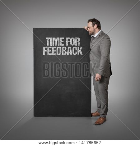 Time for feedback text on blackboard with businessman standing side