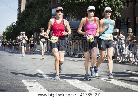 NEW YORK CITY -  JULY 24 2016: Athletes running in the NYC Triathlon Race on West 72nd St and into Central Park. The run is 10k and the race is the only International Distance triathlon in the city.