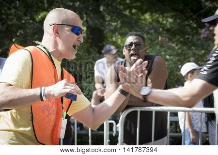 NEW YORK CITY -  JULY 24 2016: A volunteer high-fives runners as the athletes compete in the NYC Triathlon Race in Central Park. The run is 10k and the race is the only International Distance triathlon in NYC.
