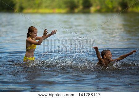 Two little cute girls frolic in the river.
