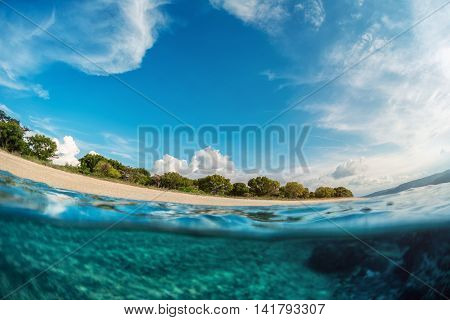 Split shot of a sea bottom and tropical island with cloudy sky above sea surface