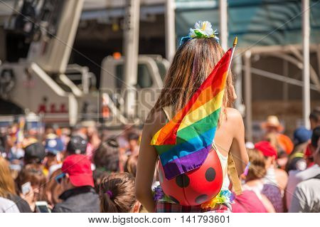 A female spectator with a rainbow flag is watching the gay pride parade in Toronto Canada.