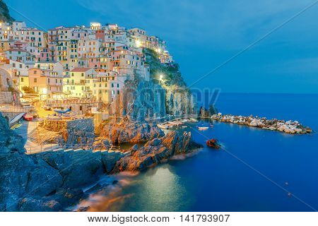 A view of the colorful traditional houses on the rock on sunset. The coast of Liguria. Manarola. Cinque Terre.