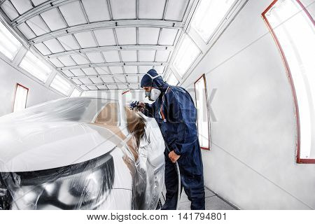 worker painting a white car in a special garage, wearing a costume and protective gear.