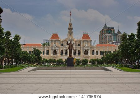 Saigon french government building with the statue of Ho Chi Minh in the front. Gardens with green grass and trees. Front (face) view. Ho Chi Minh City South Vietnam
