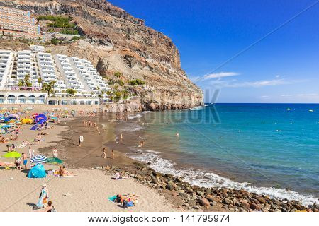TAURITO, GRAN CANARIA, SPAIN - APRIL 24, 2016: Tourists on sun holidays at the Taurito beach, Gran Canaria. Taurito is very popular tourist destination