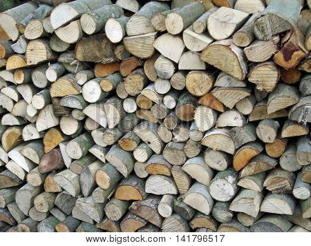Split logs drying in a stack and making an attractive collage of interlocked cut log ends. Could be used as a background texture.