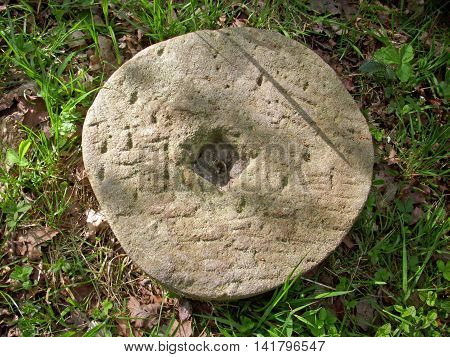 Very well worn millstone lying on the ground in woodland surrounded by grass. Could have been used to sharpen forestry tools.