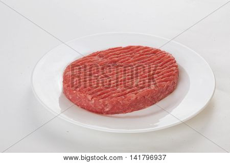 raw beef patties on a plate isolated white background
