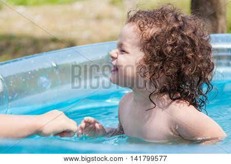 Baby girl bathes in inflatable pool outdoors