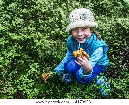 Little girl in the forest gather up a few mushrooms chanterelles.