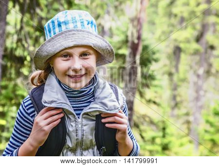 Young girl travels the forests with a backpack.